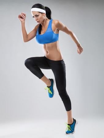 アスリート: ジョギング女性分離された白で美しい若い背景色は、補正後 写真素材