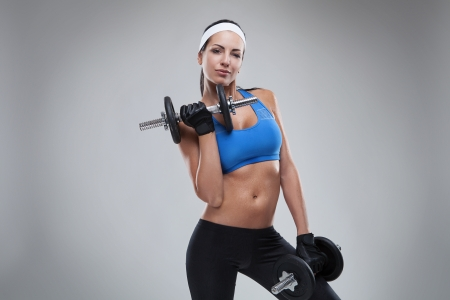 Beautiful young jogging woman exercises with dumbbells Isolated over white background  colored, retouched