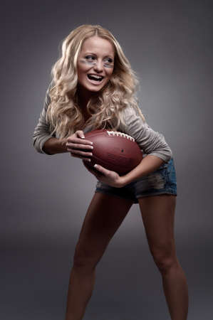 beautiful girl holding a ball for american football photo