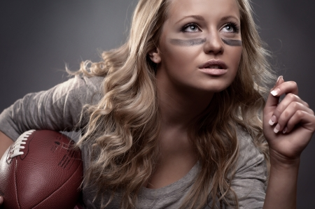 females: beautiful girl holding a ball for american football Stock Photo
