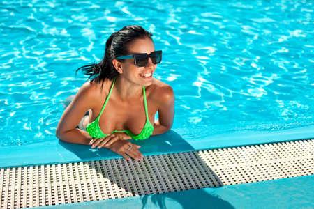 Cute happy bikini woman with nice breast in swimming pool with copy space photo