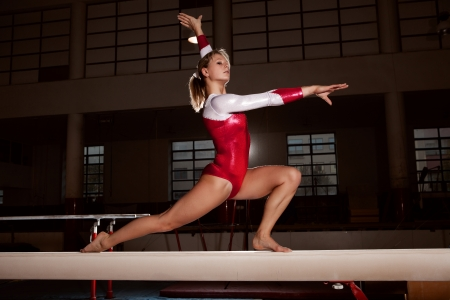 balance beam: portrait of young gymnasts training in the stadium