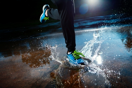 run woman: Single runner running in rain and making splash in puddle