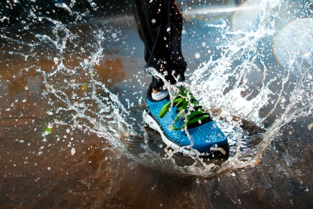water shoes: Single runner running in rain and making splash in puddle
