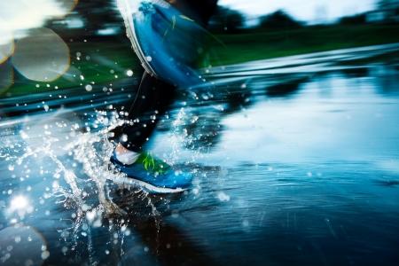 hacer footing: Corredor individual corriendo en la lluvia y hace el chapoteo en el charco Foto de archivo