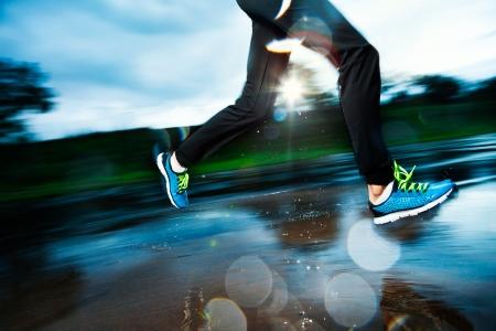 Single running in de regen en het maken van plons in plas