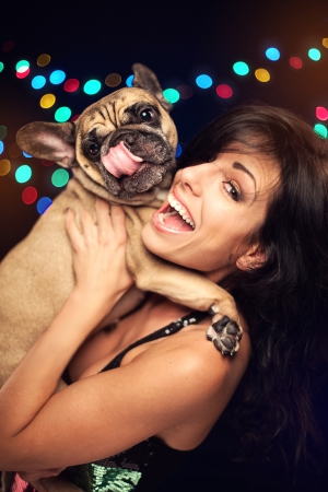 french model: Happy woman with french bulldog on New Year day party on black background with color lights