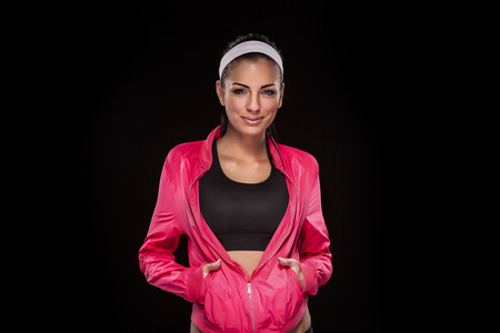 retouched: young brunette woman in jogging clothes after sportive exercise isolated on black (colored, retouched) Stock Photo
