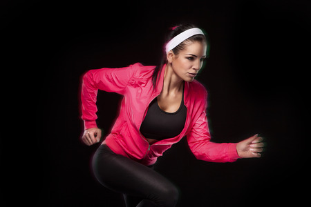 retouched: Beautiful young jogging woman. Isolated over black background (colored, retouched)
