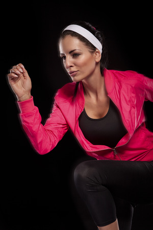woman black background: Beautiful young jogging woman isolated over black background (colored, retouched) Stock Photo