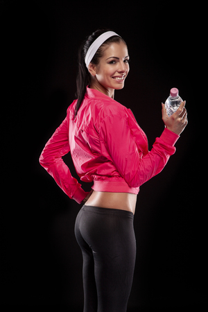 young brunette woman after sportive exercise and holding the bottle of watter isolated on black (colored, retouched)