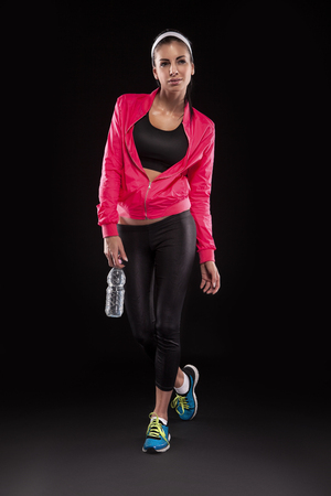 young brunette woman in jogging shoes after sportive exercise and holding the bottle of watter isolated on black (colored, retouched)