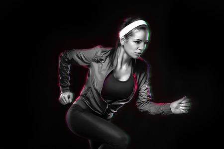 Mooie jonge vrouw joggen. Geïsoleerde over zwarte achtergrond (gekleurd, geretoucheerd)