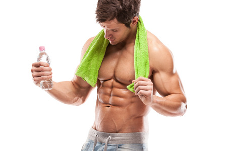 6 pack: Strong Athletic Man Fitness Model Torso showing six pack abs  holding bottle of water and towel Stock Photo