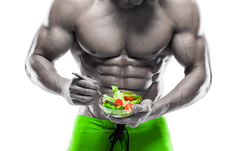 bodybuilding: Shaped and healthy body man holding a fresh salad bowl