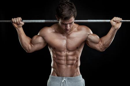 culturista: Chico culturista muscular que hace ejercicios con pesas sobre fondo negro