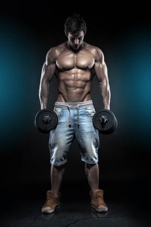 muscle training: Muskul�s Bodybuilder Kerl machen �bungen mit Hanteln auf schwarzem Hintergrund Lizenzfreie Bilder