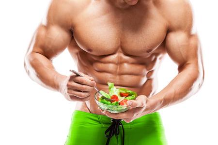musculos: Formado y saludable cuerpo del hombre que sostiene un cuenco de ensalada fresca Foto de archivo