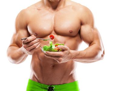 culturista: Formado y saludable cuerpo del hombre que sostiene un cuenco de ensalada fresca Foto de archivo