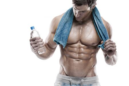 Sterke Atletische Mens Fitness Model Torso toont zes pack abs. met een fles water en een handdoek Stockfoto