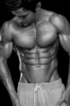 tatouage sexy: Forte homme sportif Fitness Model Torso montrant six pack abs. isolé sur fond noir Banque d'images