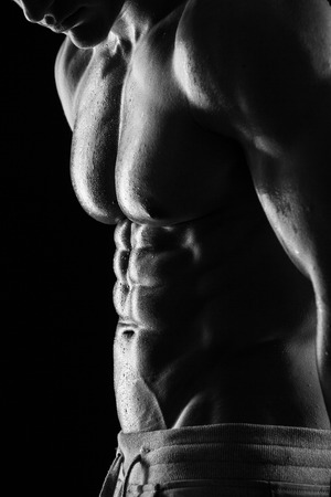 shirtless man: Strong Athletic Man Fitness Model Torso showing six pack abs. isolated on black background