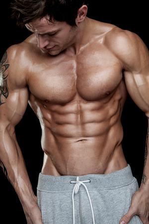 modelos hombres: Fuerte Hombre Atl�tico Modelo Fitness Torso mostrando paquete de seis abs. aislado en el fondo negro Foto de archivo
