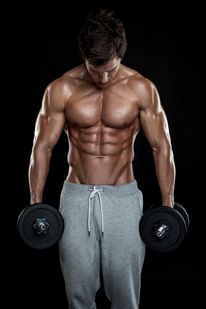Muscular bodybuilder guy doing exercises with dumbbells over black background photo