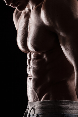 shirtless men: Strong Athletic Man Fitness Model Torso showing six pack abs. isolated on black background