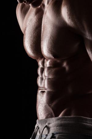 shirtless: Fuerte Hombre Atl�tico Modelo Fitness Torso mostrando paquete de seis abs. aislado en el fondo negro Foto de archivo