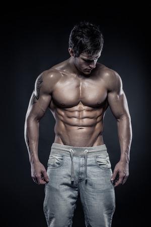 Sterke atletische mens Fitness Model Torso toont zes pack abs. geïsoleerd op zwarte achtergrond