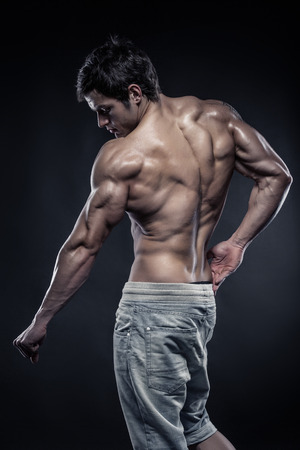 latissimus: Strong Athletic Man Fitness Model posing back muscles, triceps, latissimus