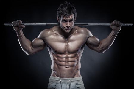 Muskulös Bodybuilder Kerl machen Übungen mit Hanteln auf schwarzem Hintergrund Standard-Bild - 27301527