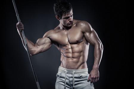 Muscular bodybuilder guy doing posing with dumbbells over black background