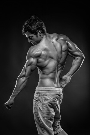 pectorals: Strong Athletic Man Fitness Model posing back muscles, triceps, latissimus
