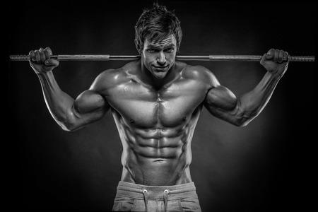 黒の背景上ダンベル体操の筋肉ボディービルダー男 写真素材