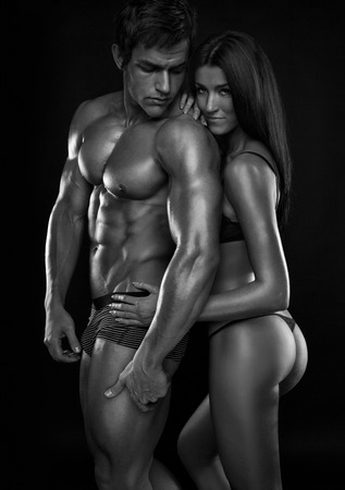 naked black men: half-naked sexy couple, beautiful woman holding a muscular man isolated on a black background Stock Photo
