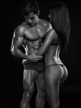 desnudo masculino: semidesnuda pareja sexy, hombre musculoso sosteniendo una hermosa mujer aislada en un fondo negro Foto de archivo