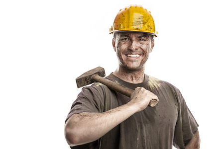 mire: Young dirty Worker Man With Hard Hat helmet holding a hammer isolated on White Background Stock Photo