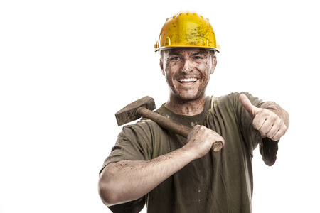 Young dirty smiling Worker Man With Hard Hat helmet holding a hammer isolated on White Background Standard-Bild