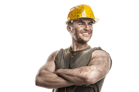 overalls: portrait of dirty worker with helmet crossed arms isolated on white background