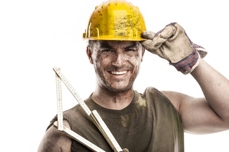 portrait of dirty worker with helmet measuring with classic wood meter isolated on white background Stock Photo