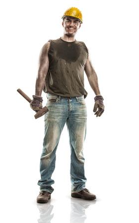 Jonge vuile werknemer man met harde hoed helm met een hamer geïsoleerd op een witte achtergrond