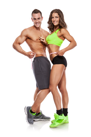 beautiful young sporty couple with a measuring tape isolated over white background Stock Photo