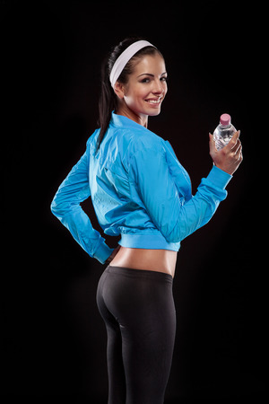 young brunette woman after sportive exercise and holding the bottle of watter isolated on black  colored, retouched