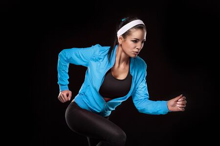 woman black background: Beautiful young jogging woman. Isolated over black background (colored, retouched)