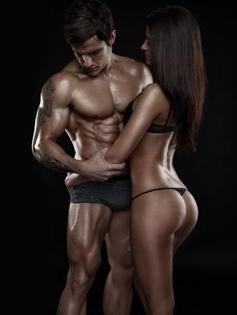 nudo maschile: mezzo nudo coppia sexy, l'uomo muscoloso in possesso di una bella donna isolato su uno sfondo nero