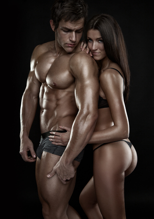 half-naked sexy couple, beautiful woman holding a muscular man isolated on a black background Stock Photo