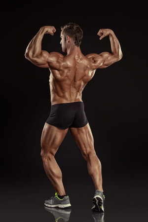 Strong Athletic Man Fitness Model posing back muscles, triceps, latissimus over black background 版權商用圖片