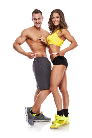 abdominal muscles: beautiful young sporty couple with a measuring tape isolated over white background Stock Photo